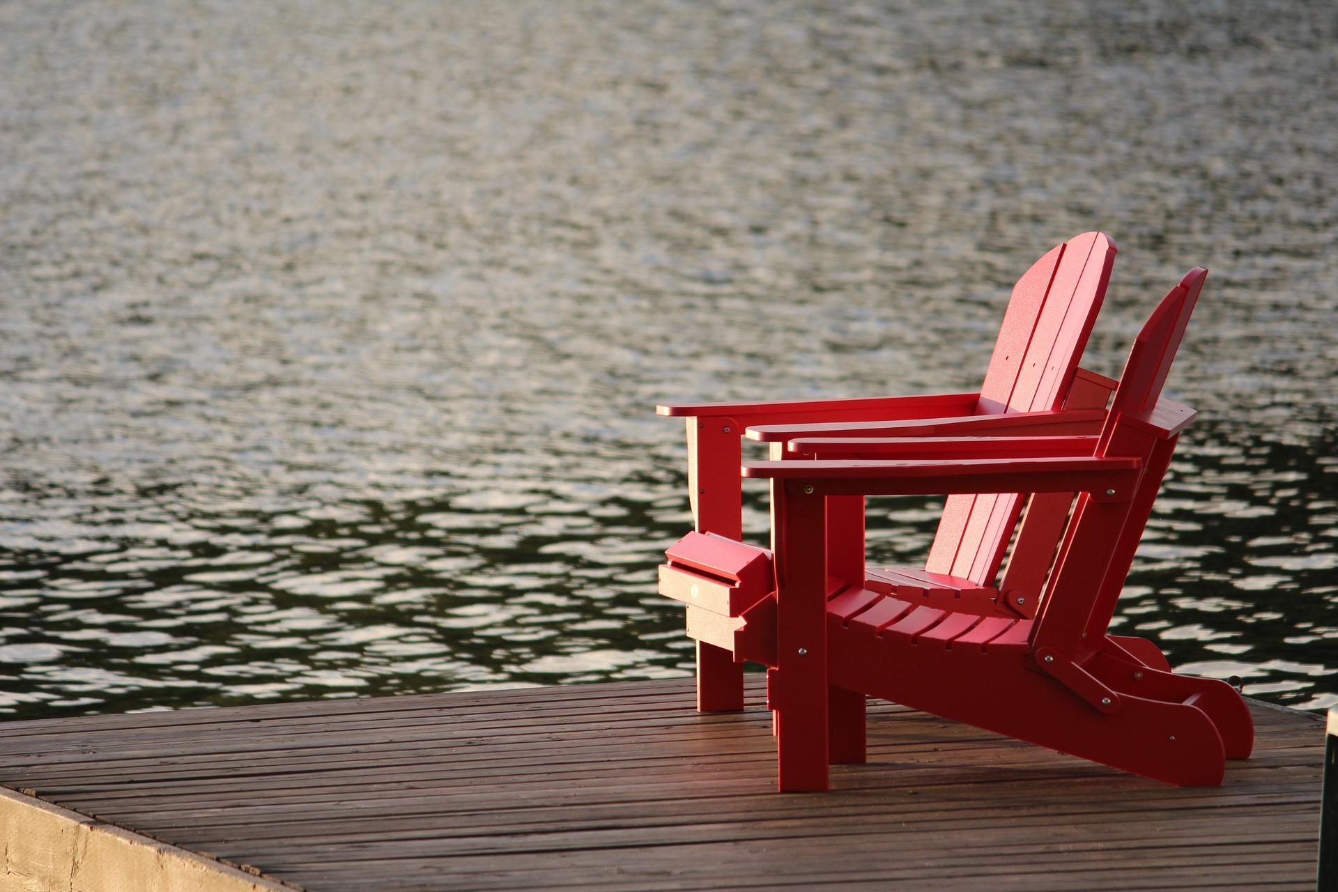 two red chairs overlooking water